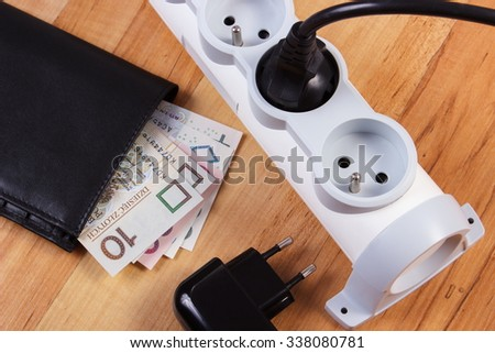 Electrical power strip with plugs and polish currency money with black leather wallet, concept of saving money on electricity - stock photo