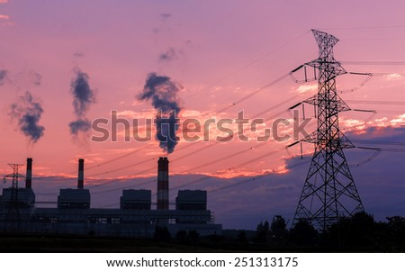 Electrical power tower and industrial site with smoking chimneys, steam against cloud sky