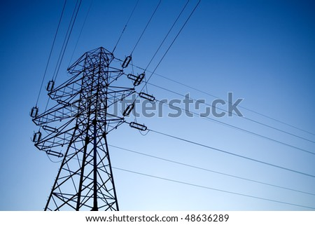 Electrical pylon silhouette over blue sky