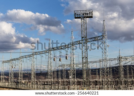 Electrical pylons and high voltage wires in electric power substation - stock photo