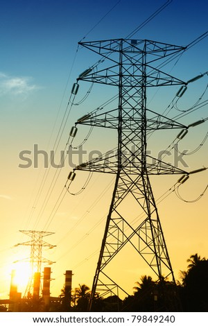 electrical pylons at blue and orange sunset - stock photo