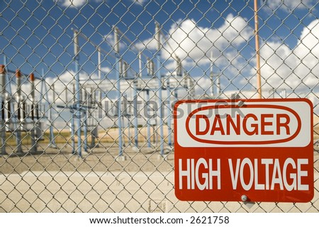 Electrical substation with 'High Voltage' sign. - stock photo