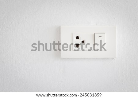 Electrical switch and plug on wall - stock photo