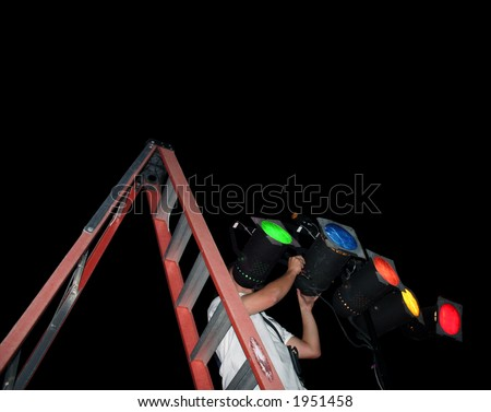 Electrical technician on a ladder adjusting stage lights. Clipping Path. - stock photo