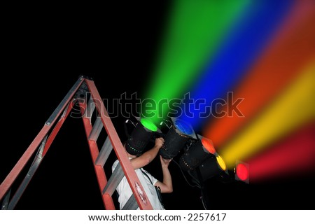 Electrical technician on a ladder adjusting stage lights. Clipping Path.