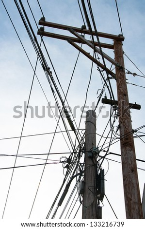 Electrical, telephone and cable lines are tangled on two adjacent utility poles.
