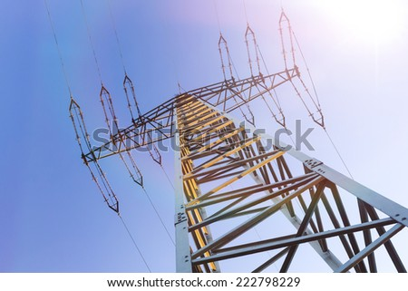 electrical tower and sun in blue sky - stock photo