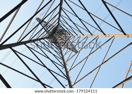 electrical tower seen from a different angle - bottom side against the blue sky