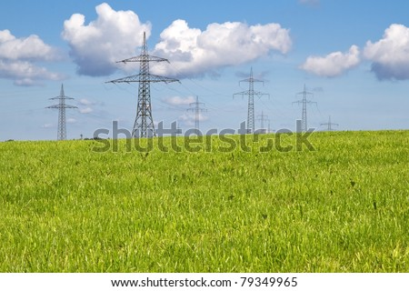 Electrical towers on a meadow in spring time - stock photo