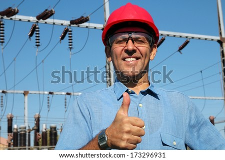 Electrical Utility Worker. Electricity distribution. Thumb up given by smiling engineer next to electrical substation.  - stock photo