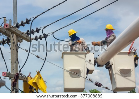 electrical utility worker in a bucket fixes a problem with a power line. - stock photo