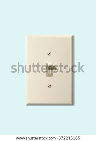 electrical wall switch with cover plate on blue wall - stock photo