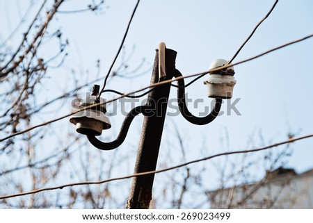 Electrical wire on pole. chaotic wire with nest on pole and blue sky background - stock photo