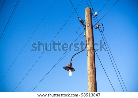 Electrical wooden pylon, cables, wires and blue sky - stock photo