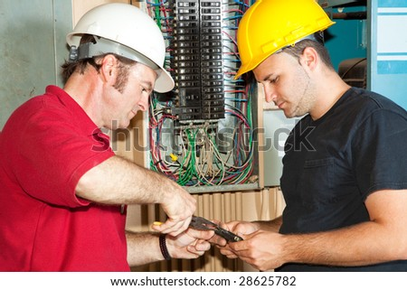 Electrician and apprentice repairing a circuit breaker from an industrial panel. - stock photo