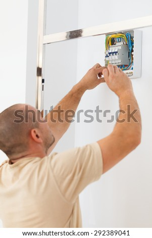 Electrician assembling electric fuse on wall with screw driver. - stock photo
