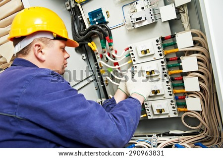 Electrician Builder At Work With Tester Measuring High Voltage And Current  Of Power Electric Line In
