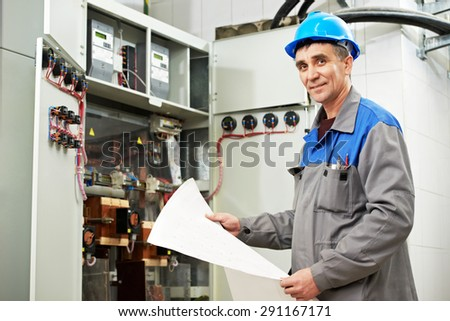 electrician builder engineer inspector with electrical scheme plan near the fuse box - stock photo