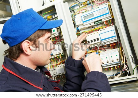 electrician builder engineer screwing equipment in fuse box