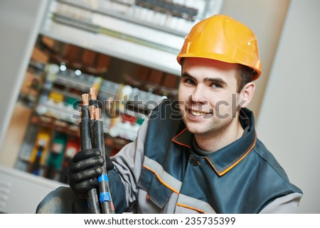 electrician builder engineer worker in front of fuse switch box with cable - stock photo
