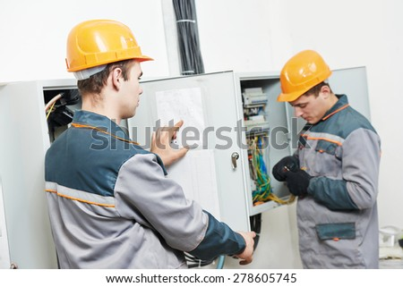 electrician builder engineer workers with electric cable wiring of fuse switch box - stock photo