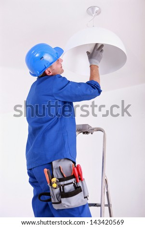 Electrician changing bulb - stock photo