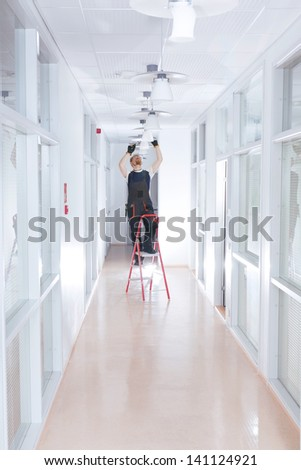 Electrician Changing Light on Ladders