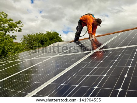 Electrician checking solar panels - stock photo