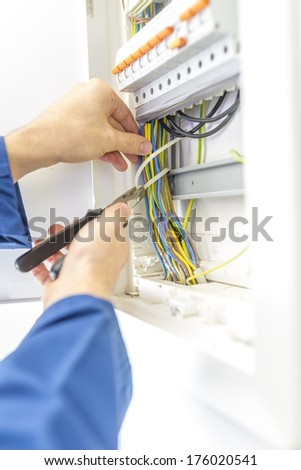 Electrician checking the wiring in a fuse box providing the electrical supply to a domestic residence either during installation as a new build or when called in to do maintenance and repairs. - stock photo