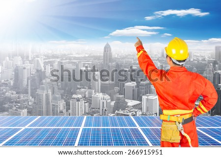 Electrician climbing ware and pointing something and solar energy panels on high building against beautiful sky with in concept ecology and real estate - stock photo