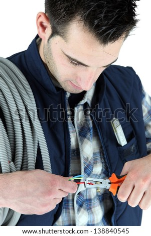 Electrician clipping electric cable - stock photo
