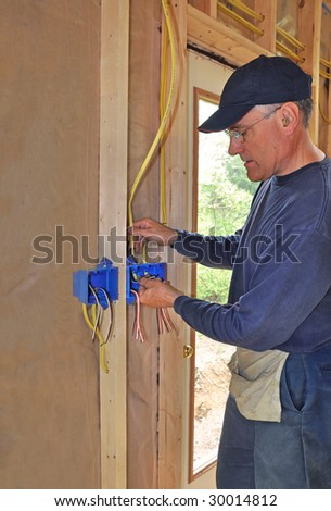 Electrician connecting wire to electrical box - stock photo