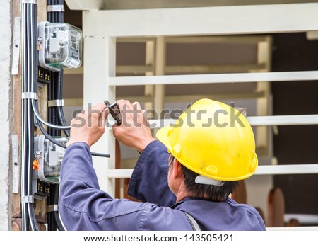 Electrician connects a Power meter. - stock photo