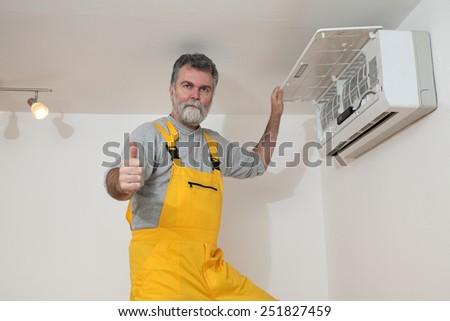 Electrician examine or install air condition device, gesturing with thumb up - stock photo