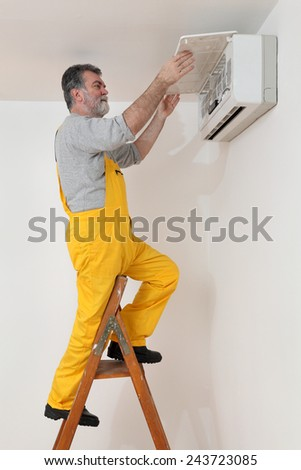 Electrician examine or install air condition device in a room - stock photo