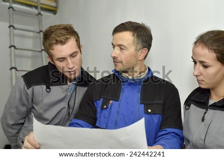 Electrician explaining trainees building electric plan  - stock photo