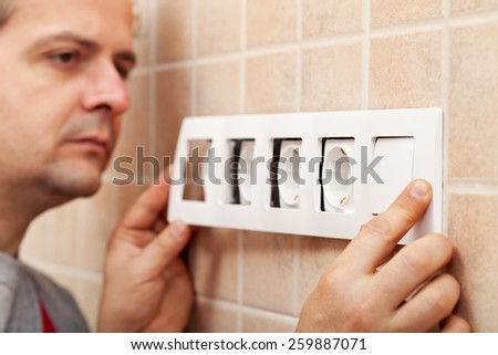 Electrician finished installing a wall fixture - snapping the decorative frame into place - stock photo