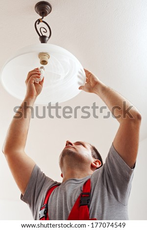 Electrician finished mounting ceiling lamp - installing a fluorescent lightbulb - stock photo