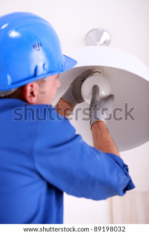 Electrician fitting a ceiling light - stock photo