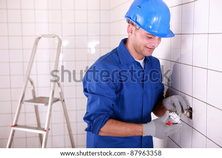 Electrician fitting a light switch