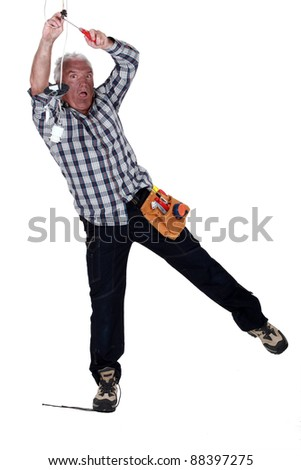 electrician fixing the installation and having an electrical shock - stock photo