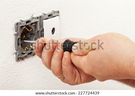 Electrician hand mounting a wall fixture - fastening the screws - stock photo