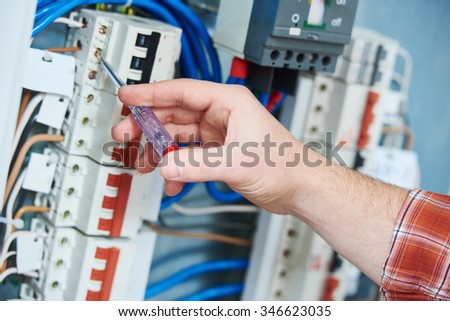 electrician hand with electric test screwdriver checking voltage of switching electric actuator equipment in fuse box - stock photo