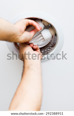 Electrician hands assembling ecological light in ceiling. - stock photo