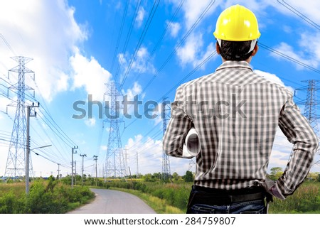 Electrician holding blueprint high voltage power stock photo electrician holding blueprint at high voltage power pylon against blue sky malvernweather Choice Image