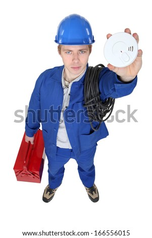 Electrician holding smoke alarm - stock photo