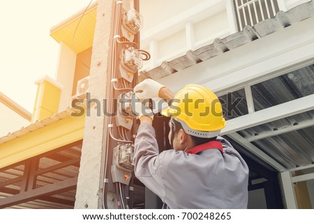 Electrician in a gray uniform wears gloves and a helmet installing a power meter on an electricity pole.