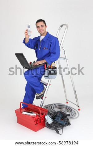 Electrician in overalls with a mobile phone and a laptop computer on white background