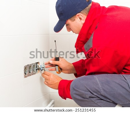 Electrician in protective workwear installing current outlet. - stock photo
