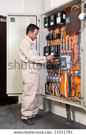 Electrician inspecting wires in electric panel - stock photo